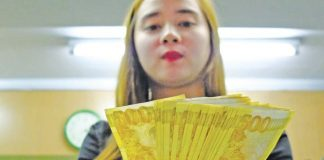 A bank teller counts 500-peso bills at a private bank in Metro Manila. ALAMY