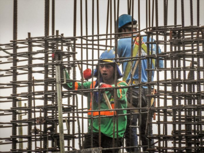 Filipino workers install steel rods at a construction site in Metro Manila. Economic managers on Wednesday cut the range of growth target to six to 6.5 percent this year, and 6.5 to 7.5 percent for 2021-2022. FIVEPRIME