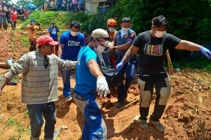 Responders carry one of the body of the three brothers who died due to suffocation inside an underground water tank in Barangay Maindang, Cuartero, Capiz on Wednesday. PDRMMO CAPIZ