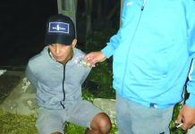 Drug suspect Christopher Benignos of Barangay Dumlog, Malay, Aklan sits handcuffed after police officers caught in an entrapment operation. Benignos allegedly sold a sachet of marijuana to a poseur-buyer on July 13. PDEA REGION 6