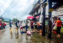 "WATER, WATER EVERYWHERE. Residents of Barangay San Nicolas in Iloilo City's La Paz district wade through murky floodwater after a heavy downpour. Other parts of the city with clogged drainage have this problem, too. Monsoon rains enhanced by tropical depression ""Falcon"" also forced the city government to suspend classes yesterday, July 16, 2019. IAN PAUL CORDERO/PN"
