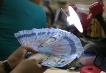 A teller inspects one thousand pesos bills inside a money changer in Manila. REUTERS