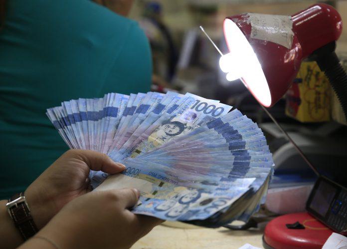 A teller inspects one thousand pesos bills inside a money changer in Manila. REUTERS