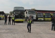 Policemen secure Ceres buses at the Dynamic Builders compound in Barangay Alijis, Bacolod City. ARCHIE REY ALIPALO/PN