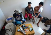BUSTED DRUG SUSPECTS. Edwin Balinas of Santa Barbara, Iloilo and Janry Napat of Nabas, Aklan look on while an undercover policeman in civilian attire (left) checks the items recovered from them inside a house at a residential subdivision in Barangay Jibao-an, Pavia, Iloilo on Aug. 16, 2019. Sachets of suspected shabu valued at P810,000 were seized. IAN PAUL CORDERO/PN