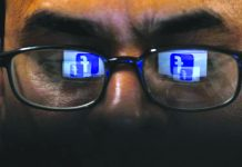 Facebook logo is reflected in glasses in this picture illustration taken April 1, 2019. REUTERS