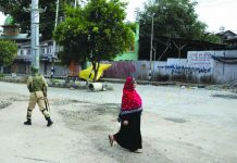 A Kashmiri woman walks past an Indian paramilitary soldier who prepares to block a road with barbed wires during security lockdown in Srinagar, Indian controlled Kashmir, Sunday, Aug. 18, 2019. AP