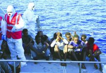 Migrants are evacuated by Italian Coast guards from the Open Arms Spanish humanitarian boat at the coasts of the Sicilian island of Lampedusa, southern Italy, Saturday, Aug. 17, 2019. AP