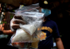 A member of the Philippine National Police investigation unit shows confiscated methamphetamine, known locally as shabu, along with Philippine peso bills seized from suspected drug pushers during an operation by the police in Quiapo, Manila on July 3, 2016. REUTERS