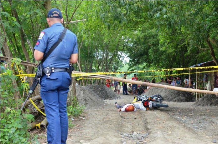 AMBUSH SITE. A policeman inspects this crime scene in Barangay Cabugao Norte, Santa Barbara, Iloilo where a farmer was fatally ambushed while driving his motorcycle yesterday morning, Sept. 11, 2019. Probers say the attack could have been sparked by a land dispute. IAN PAUL CORDERO/PN