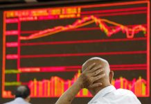 An investor looks at an electronic board showing stock information at a brokerage house in Beijing, China, August 25, 2015. Asian shares and United States stock futures dipped on Wednesday after British lawmakers rejected the government's timetable to fast-track legislation for its deal to take Britain out of the European Union. KIM KYUNG-HOON/REUTERS