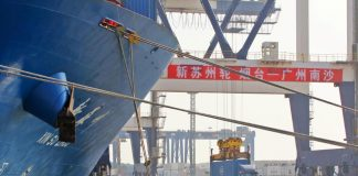 A crane lifts a container from a truck next to a cargo vessel at a port in Yantai, Shandong province, China Oct. 17. China's economy expanded at its slowest rate in nearly three decades during the third quarter as it was hit by the long-running United States trade war and cooling domestic demand. REUTERS
