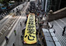 "People march with a banner to protest against ""the abuse of pro-democracy protesters by police,"" near Chater Garden in Central district, Hong Kong, China on Oct. 18. REUTERS/AMMAR AWAD"
