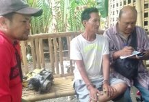 Jimmy Ramos (second from right) sits handcuffed after he was arrested for illegal possession of firearm in Barangay Jalas, New Washington, Aklan last week. RADYO TODO/PN