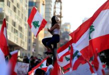 A demonstrator sits on a pole while carrying a national flag during an anti-government protest in downtown Beirut, Lebanon on Oct. 20. REUTERS/ALI HASHISHO