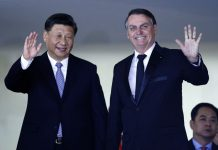 China's President Xi Jinping, left, and Brazil's President Jair Bolsonaro wave to reporters upon Xi Jinping's arrival for a bilateral meeting on the sidelines of the 11th edition of the BRICS (Brazil, Russia, India, China and South Africa) Summit, at the Itamaraty Palace in Brazil, on Nov. 13. ERALDO PERES/AP PHOTO