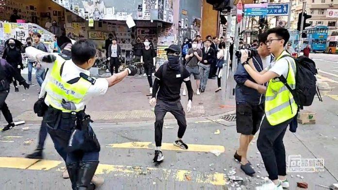 A still image from a social media video shows a police officer aiming his gun at a protester in Sai Wan Ho, Hong Kong, China on Nov. 11. CUPID PRODUCER VIA REUTERS