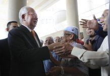 Former Malaysian prime minister Najib Razak, left, greets supporters as he arrives at Kuala Lumpur High Court in Kuala Lumpur, Malaysia, Nov. 11. An important court ruling Monday in the first corruption trial of Najib will be a test of the legal system and of the credibility of the prime minister who brought about his shocking ouster from office last year. VINCENT THIAN/AP