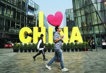 "A man eats a snack while passing an ""I love China"" decoration at a popular shopping mall in Beijing. China put a positive face Saturday on a first-step trade agreement that dials down a trade war it blames the United States for starting. AP"
