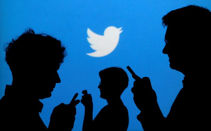 People holding mobile phones are silhouetted against a backdrop projected with the Twitter logo taken in Warsaw, Poland. Twitter co-founder Jack Dorsey is funding research with the goal of changing the way information circulates on social media – with the aim of combating online violence, hate and disinformation. REUTERS