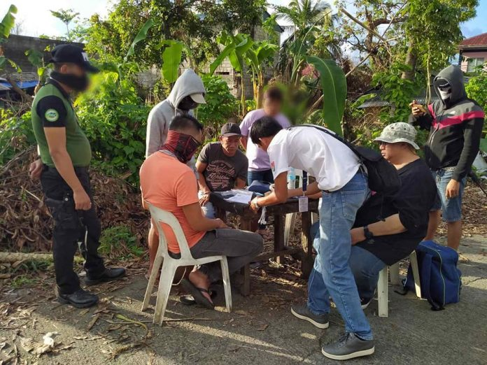 Antidrug officers inspect the seized items from drug suspect Omar Bacuta during an entrapment operation in Barangay Poblacion, Numancia, Aklan on Jan. 18. PDEA REGION VI-WESTERN VISAYAS