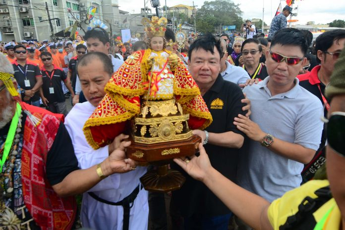 Reverend Father Edcel Alcayaga of the Parish of San Jose de Placer and Mayor Jerry Treñas of Iloilo City carry the Señor Santo Niño for a foot procession after the fluvial parade at the Iloilo River.