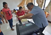 An election officer helps a person with disability feed her ballot into the vote-counting machine during a simulation voting at Central Philippine University in Iloilo City on Jan. 21, 2019. The simulation is a project of the Commission on Elections to further fine-tune the voting processes for persons with disability. IAN PAUL CORDERO/PN