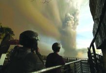 """People watch from Tagaytay as plumes of smoke and ash rise from Taal Volcano on Jan. 12. The Philippine Institute of Volcanology and Seismology said """"hazardous explosive eruption"""" is still imminent in the locality. AARON FAVILA/AP/CNN.COM"""