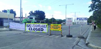 The Department of Public Works and Highways installed this road closure signs leading to the Aganan Bridge in Barangay Aganan, Pavia, Iloilo on Saturday. The decade-old bridge rendered impassable as workers started repairing its damaged portion. IME SORNITO/PN