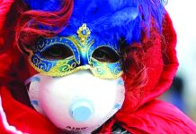 A Carnevale di Venezia participant in Italy wears two masks – a carnival mask for the festival and a facemask to avoid catching a new coronavirus. BBC