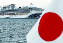 The cruise ship Diamond Princess is pictured beside a Japanese flag as it lies at anchor while workers and officers prepare to transfer passengers who tested positive for coronavirus, at Daikoku Pier Cruise Terminal in Yokohama, south of Tokyo, Japan on Feb. 12, 2020. REUTERS