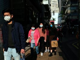 People wear protective masks as they walk outside a shopping mall at Causeway Bay, following the outbreak of the new coronavirus, in Hong Kong, China on Feb. 21, 2020. REUTERS