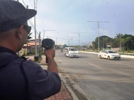 SPEED CHECK. A traffic enforcer checks the speed of these vehicles on Sen. Benigno Aquino Jr. Avenue, a traffic discipline zone in Mandurriao, Iloilo City. Drivers' lack of discipline contributes to traffic congestion and causes vehicular accidents. PN PHOTO