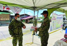 Western Visayas police director Brigadier General Rene Pamuspusan (left) gives boxes of face masks and fruits to Dumarao chief of police Larnel Frial, which are to be used by personnel who conduct checkpoint at the border of Iloilo and Capiz provinces in Barangay Aglalana, Dumarao, Capiz on March 23. PIA